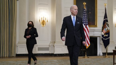 US President Joe Biden holds a face mask after speaking about efforts to combat COVID-19. Vice-President Kamala Harris is at left.
