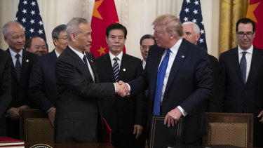 President Donald Trump and Chinese Vice Premier Liu He shake hands after signing the US-China trade agreement in the White House.