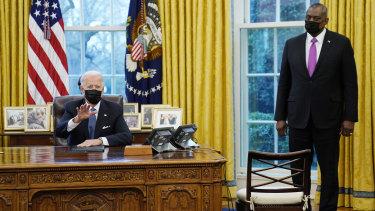 US Secretary of Defence Lloyd Austin listens as President Joe Biden speaks before singing an executive order reversing the Trump era ban on transgender serving in the military.