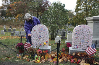 Gavin Neville, 72, places an 'I Voted' sticker on the grave of women's rights advocate Susan B. Anthony in Rochester, New York, today (Monday, US time).