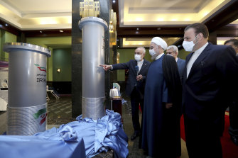 President Hassan Rouhani, second right, listens to head of the Atomic Energy Organization of Iran Ali Akbar Salehi while visiting an exhibition of Iran's new nuclear achievements in Tehran, Iran.