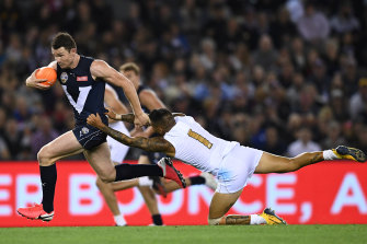 Patrick Dangerfield charges free of a tackle by the All-Stars' Michael Walters in Friday night's bushfire relief state-of-origin match at Marvel Stadium.