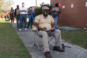 Richard Williams sits in a folding chair, filling out paperwork, as he waits in line to vote early in Savannah. Black people are going to the polls by the thousands and waiting in lines for hours to vote early.