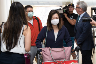 Passengers arrive at Sydney Airport from Wuhan wearing masks.