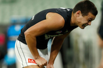 Jack Silvagni leaves the field after copping a hit from Zach Merrett.