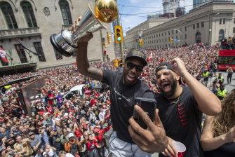 Kawhi Leonard (holding his MVP trophy) and Drake celebrate Toronto's NBA success at the parade.