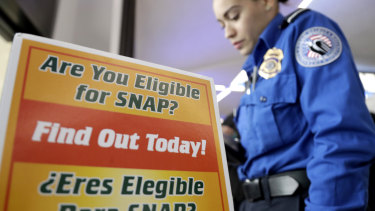 A Transportation Security Administration employee stands at a booth to learn about a food stamp program.
