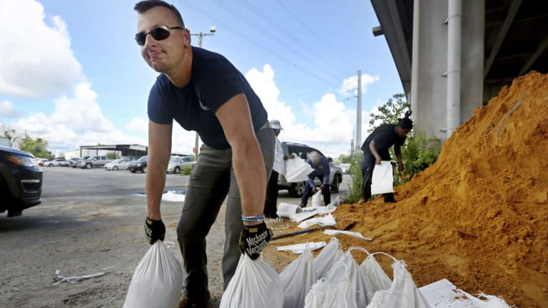 Kevin Orth loads sandbags into cars as he helps residents prepare for Hurricane Florence, in Charleston, South Carolina.