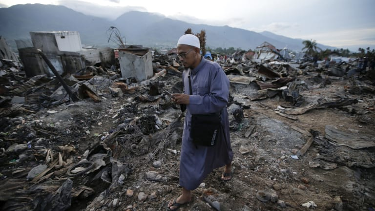 A man walks by remains of toppled houses at the earthquake damaged neighbourhood of Balaroa in Palu.