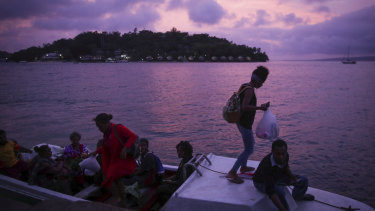 Locals board boats in Port Vila during sunset on Monday evening.