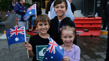 Excited attendees wave their flags at the Anzac Day March.