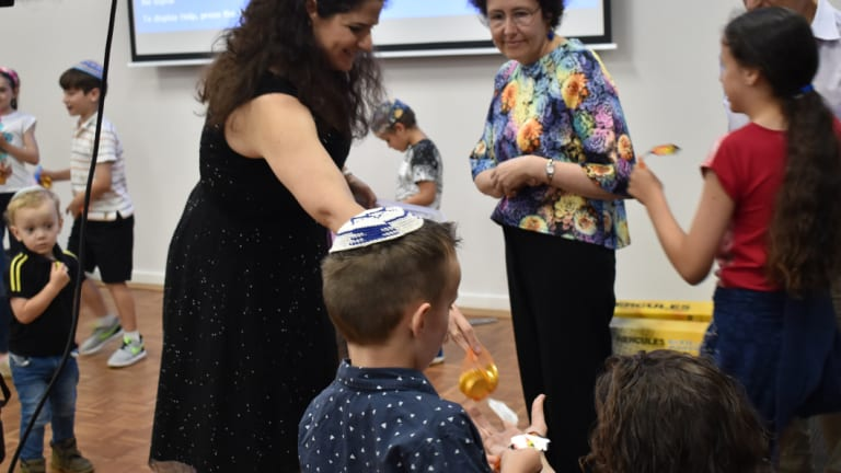 """The elders hand out bags of chocolate money to kick-off the dreidel game for the young ones attending the synagogue's """"Shabbat + Hanukkah"""" services."""