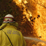 A Tuncurry fire crew member fights part of the Hillville bushfire south of Taree on the NSW Mid North Coast.