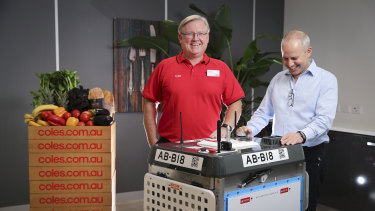 Coles CEO Steven Cain and Ocado CEO Tim Steiner with one of the robots that will handle Coles' online orders.