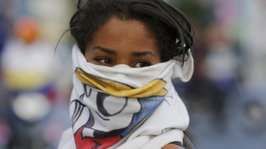 An anti-government protester takes part in a road block in Caracas, Venezuela.