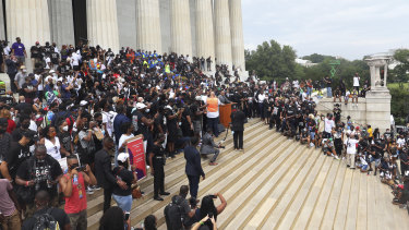 People gather at the Lincoln Memorial as they listen to the Rev. Al Sharpton speak during the March on Washington