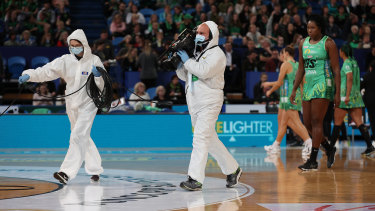 Two members of the media walk across the court wearing PPE during the round five match between the Fever and the Giants.