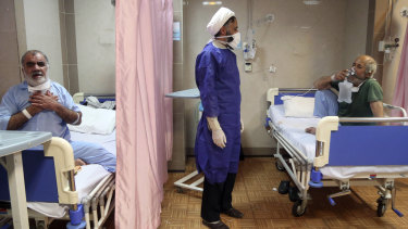 A cleric talks with a patient infected with coronavirus, at a hospital in Qom, 125 kilometres south of the capital Tehran, Iran.