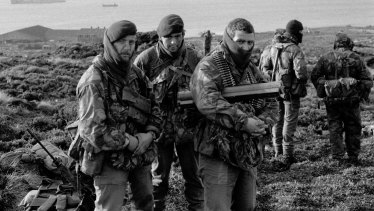 Royal Marines wait to go on patrol from Ajax Bay during the Falklands War.
