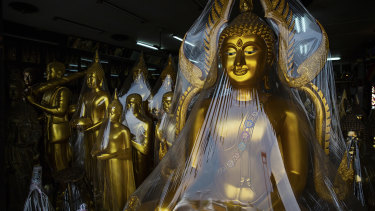 A Buddha statue and trinket shop in Bangkok, Thailand.