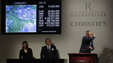 "Global president of Christie's, Jussi Pylkkanen, right, taps the gavel on the podium for the final sale at $75 million of Claude Monet's ""Nympheas en fleur"" during an auction from the collection of Peggy and David Rockefeller on May 8."