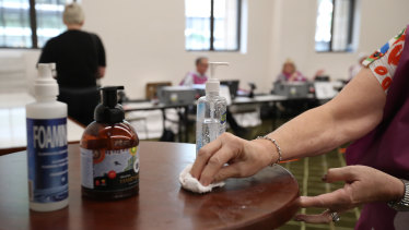 An election official uses hand sanitiser at the Brisbane City Hall polling booth on March 28.