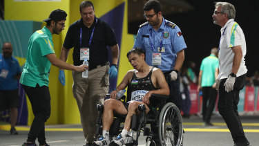 Andrey Petrov of Uzbekistan is taken away in a wheelchair after the men's marathon at Doha.