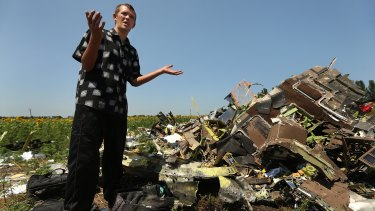 Donetsk People's Republic sniper Eugene Lukovkin stands among pilots' bags where he witnessed the front section of MH17 crashing and found the pilots bodies.