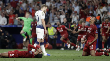 Agony, ecstasy: Harry Kane slumps off the pitch while Liverpool players celebrate.