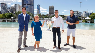 AFL chief executive Gillon McLachlan, Queensland Tourism Minister Kate Jones, former Brownlow Medallist and Brisbane Lions player Simon Black, and former Hawthorn and Brisbane Lions player Luke Hodge with the AFL premiership trophy at South Bank in Brisbane.