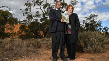 Vince Copley and Professor Claire Smith of Flinders University at Red Banks Conservation Park in Burra, SA, with a book on the Ngadjuri featuring Copley's grandfather, Barney Waria, on the cover.