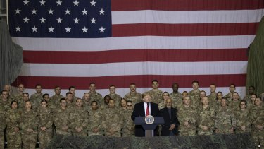 US President Donald Trump addresses members of the military during a surprise Thanksgiving Day visit last month.