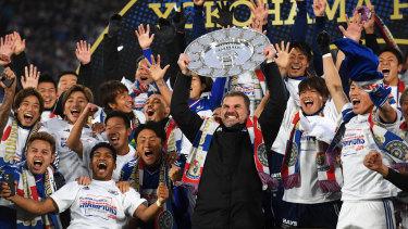 Ange Postecoglou raises the J-League trophy in triumph in Yokohama.