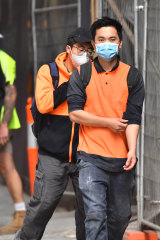 Construction workers in face masks leave a city building site.