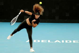 Naomi Osaka serves against Serena Williams in their Adelaide practice match.