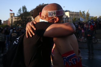 "Two men, one with a head sticker reading ""No more abuse"", embrace each other in Santiago on the day Chileans voted to create a new constitution."