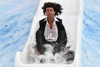 Dressed as Meat Loaf, AFL chief executive Gillon McLachlan slides into the ice bath.