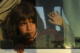A young Syrian girl peers out the window of one of the buses bring 784 Syrian refugees to Bardarash Refugee Camp in Iraqi Kurdistan.