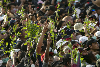 Protesters hold flowers and the three-finger salute. Thousands of anti-government protesters rallied near Government House on the anniversary of a 1973 popular uprising that led to the ousting of a military dictatorship.