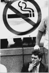A man smokes in front of an Anti-Smoking sign.