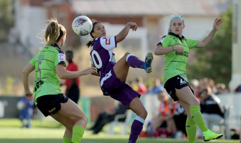 Perth star Samantha Kerr cuts between Canberra's Nikola Orgill and Ellie Carpenter.