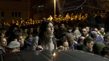 A protester stands as a crowd gathers at an entrance to the state-run TV headquarters in Belgrade, Serbia, on Saturday.