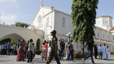 A Sri Lankan government soldier secures the premises of a Catholic church as devotees leave after Sunday Mass at a church in Colombo.