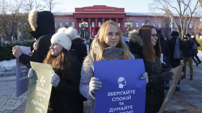 """Students hold posters reading """"Keep calm and think with your head"""" and """"Keep calm support the army"""" in front of a university in Kiev, Ukraine, after Russia seized the crew of three Ukrainian vessels."""