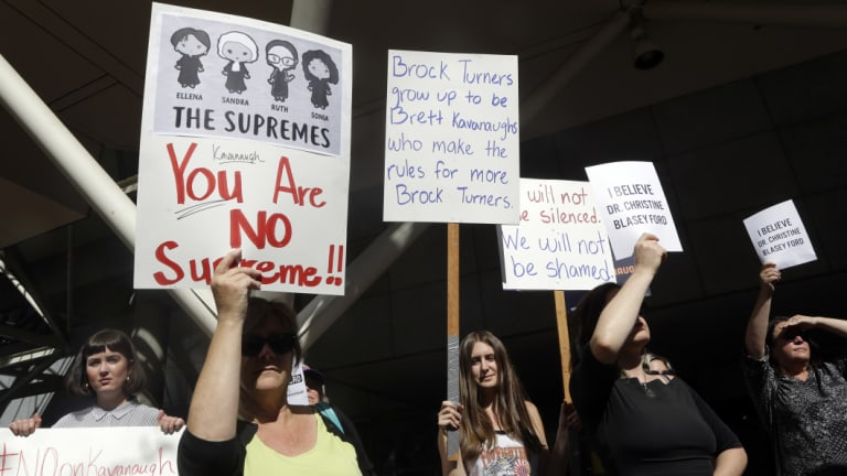 Protestors hold signs during a demonstration against the nomination of Brett Kavanaugh, in Portland Oregon.