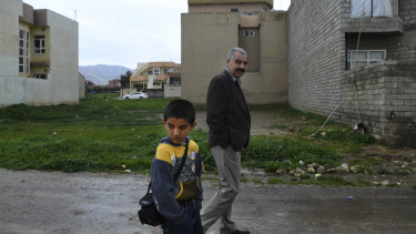 Ayham Azad walks with his uncle Tahsin Shahwan, who cares for him and his brother.