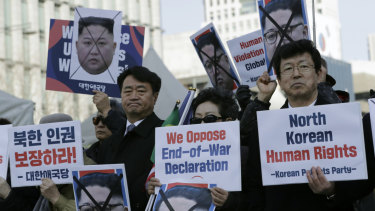 South Korean protesters and North Korean defectors hold portraits of North Korean leader Kim Jong-un during a rally urging US President Donald Trump to discuss human rights with NK's leader Kim Jong-un.