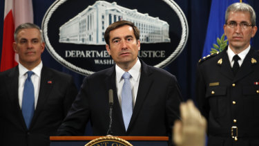 Assistant Attorney-General for National Security John Demers, centre, answers questions during a news conference.