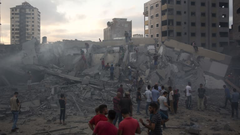 Palestinians inspect the damaged Said al-Mishal cultural centre after it was bombed by an Israeli airstrike in Gaza City on August 9.