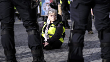 A woman sits down as other yellow vest protesters gather on the famed Champs Elysees avenue to keep pressure on French President Emmanuel Macron's government, for the 13th straight weekend of demonstrations on Saturday.
